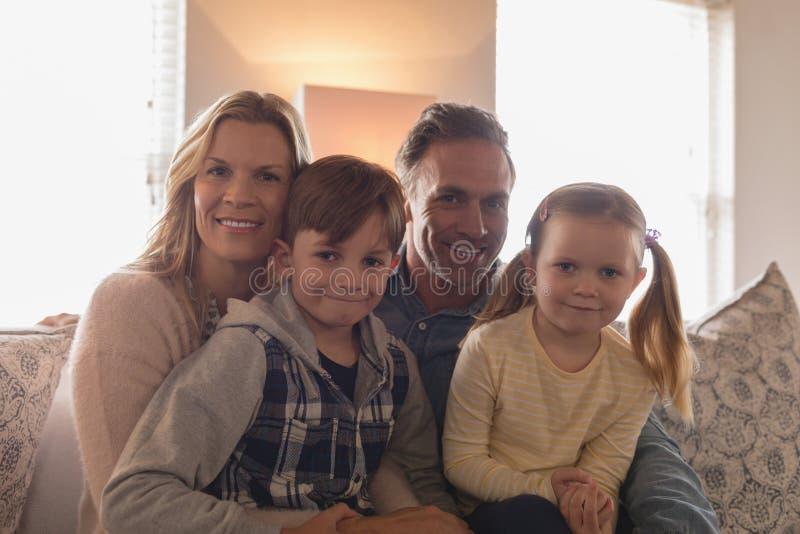 Glückliche Familie, die zusammen zu Hause auf Sofa im Wohnzimmer sitzt lizenzfreie stockfotografie
