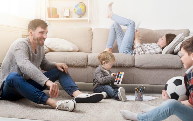 Glückliche Familie, die zusammen zu Hause auf Sofa stillsteht lizenzfreies stockbild