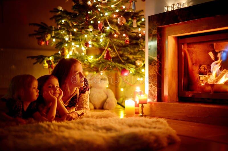 Glückliche Familie durch einen Kamin auf Weihnachten stockfoto