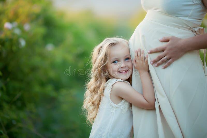 Glückliche Familie: eine junge schöne schwangere Frau mit ihrer kleinen netten Tochter, die auf dem orange Gebiet des Weizens auf stockbilder