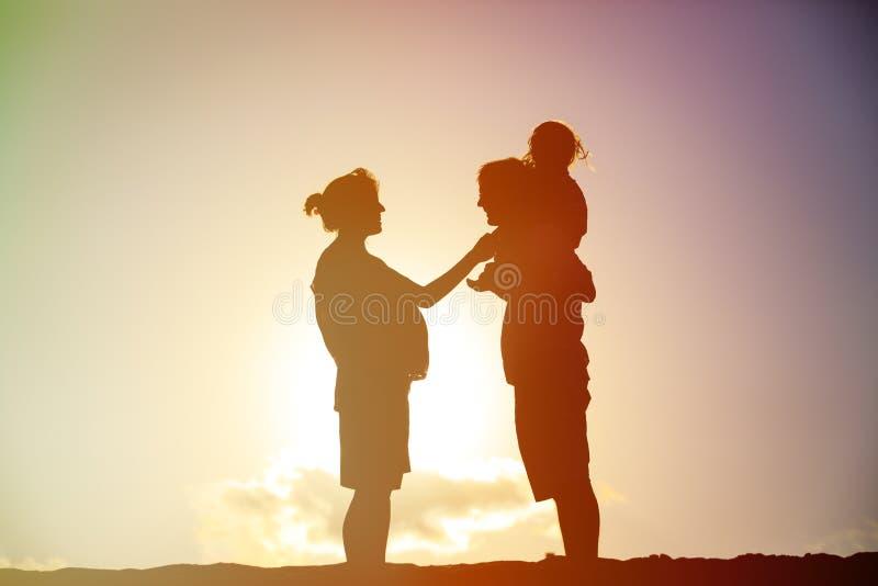 Glückliche Familie einschließlich schwangere Mutter, Vaterkleinkind bei Sonnenuntergang lizenzfreies stockbild