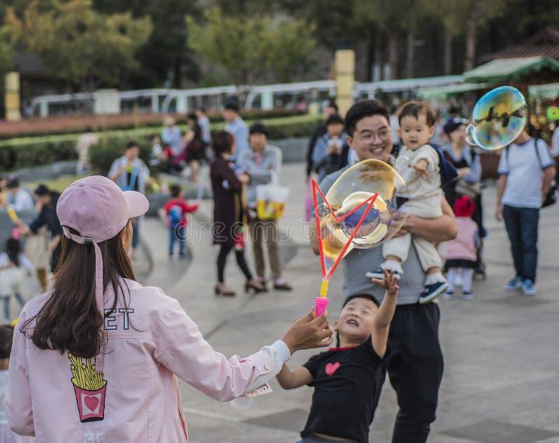 Glückliche Familie, Frau, die Seifenblasen, Kind versucht, Blasen, Ehemann zu fangen hält ein Kind rüttelt lizenzfreie stockfotos