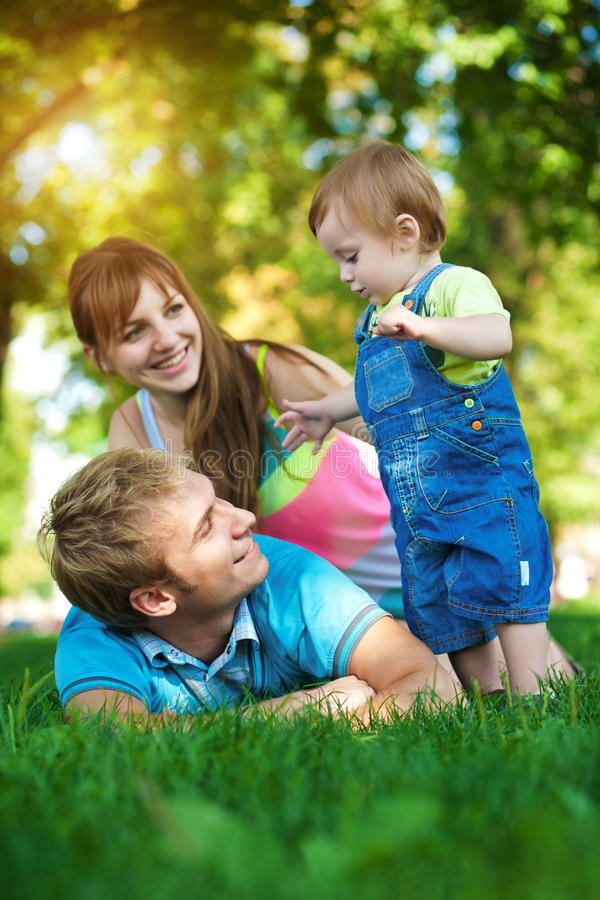 Glückliche Familie gehen in den grünen Sommerpark lizenzfreie stockfotos
