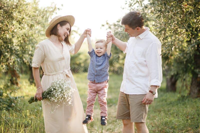 Glückliche Familie geht zusammen Frau und Mann halten ihr Kind auf Händen Sie betrachten ihn stockfoto