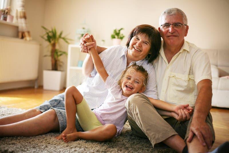 Glückliche Familie Großeltern mit Enkelin zu Hause stockfotos