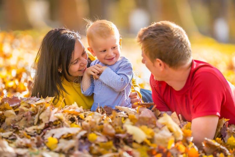 Glückliche Familie im Herbstpark, der mit Blättern spielt stockbild