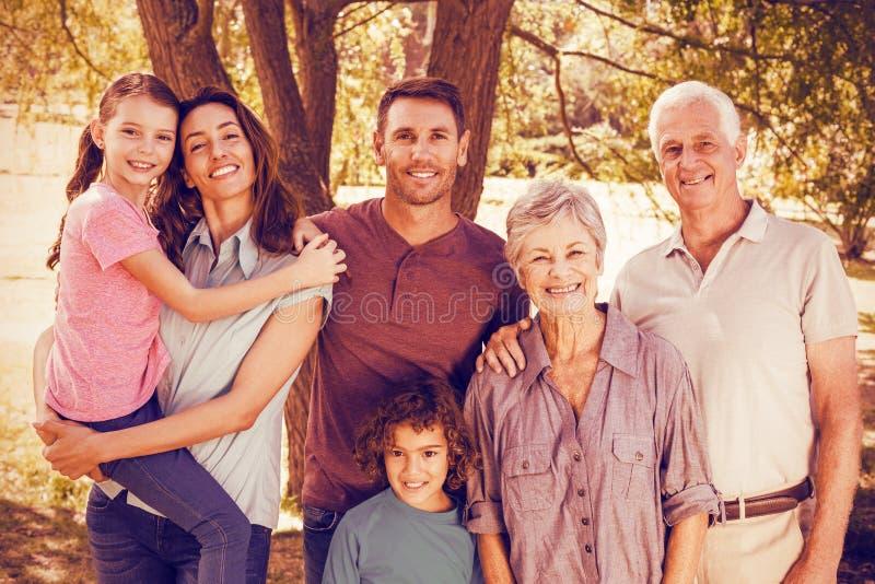 Glückliche Familie im Park durch Baum lizenzfreie stockfotografie