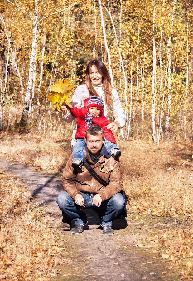 Glückliche Familie ist im herbstlichen Park lizenzfreie stockfotografie