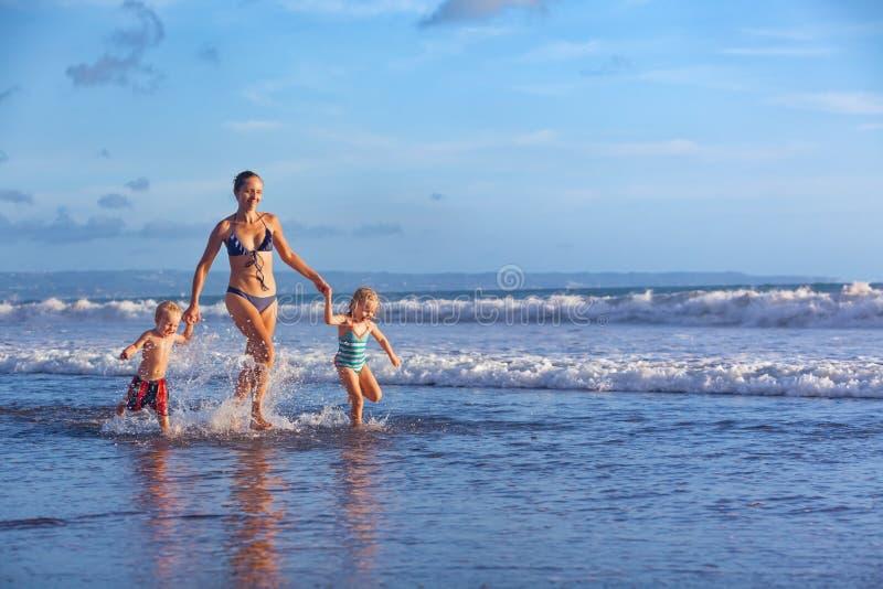 Glückliche Familie laufen mit Spaß entlang Sonnenuntergangstrandbrandung lizenzfreies stockfoto