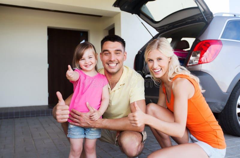 Glückliche Familie mit dem Auto, das sich Daumen am Parken zeigt lizenzfreies stockbild
