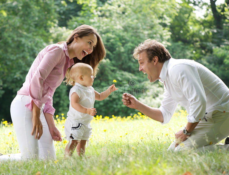 Glückliche Familie mit dem Kind, das dem Vater Blume gibt stockbild