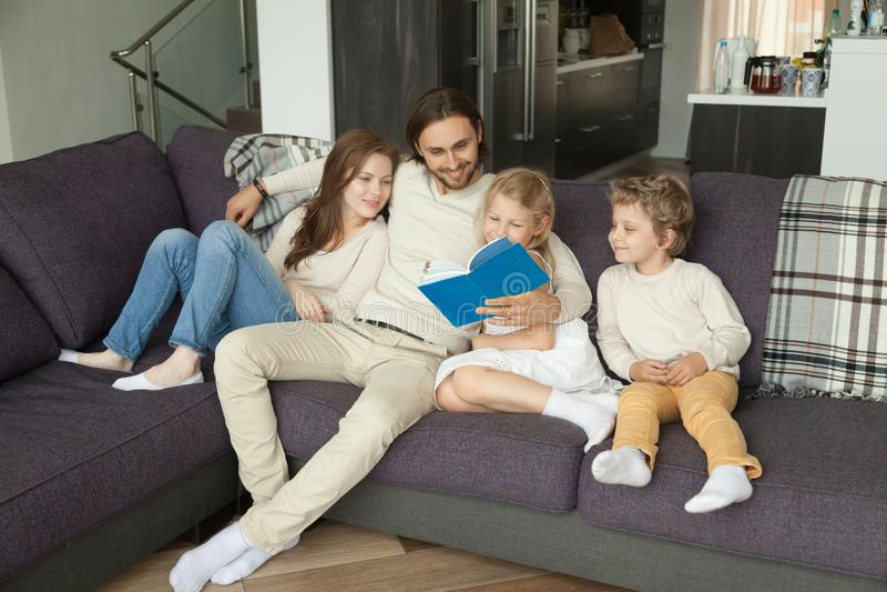 Glückliche Familie mit dem Kinderlesebuch, das zusammen auf Sofa sitzt lizenzfreie stockbilder