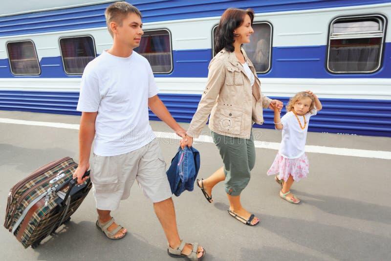 Glückliche Familie mit dem Mädchen, das auf Bahnhof geht stockfoto