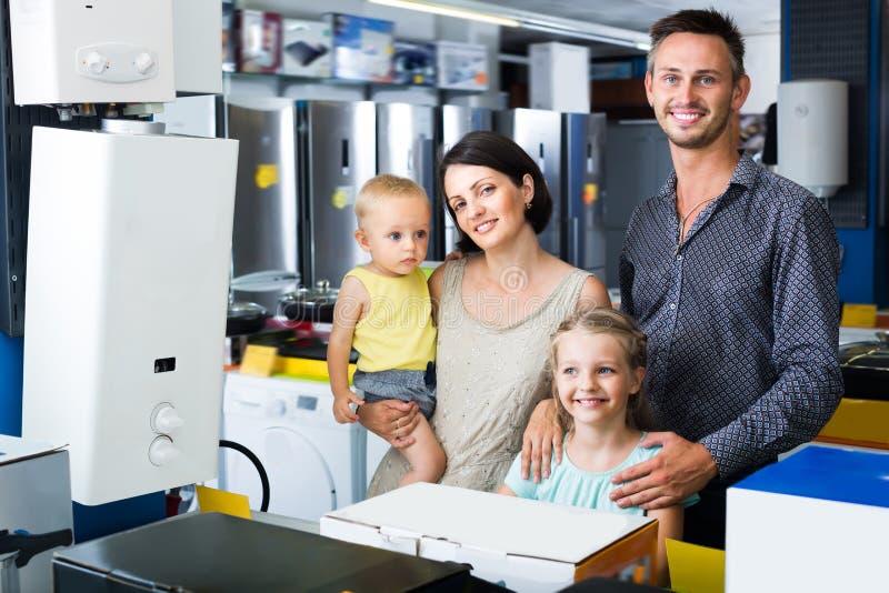Glückliche Familie mit dem zwei Kindereinkauf stockfotografie