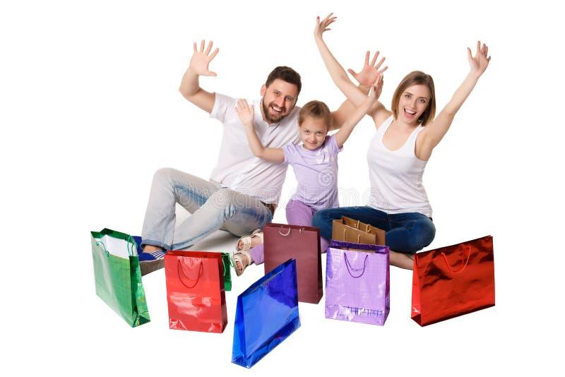 Glückliche Familie mit den Einkaufstaschen, die am Studio sitzen lizenzfreie stockbilder