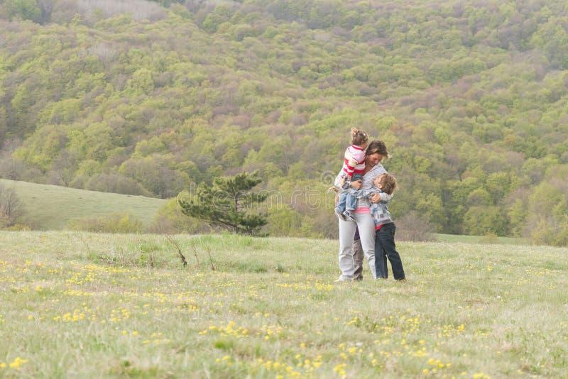 Glückliche Familie mit den Kindern, die Freizeit auf natürlichem backg genießen lizenzfreie stockfotografie