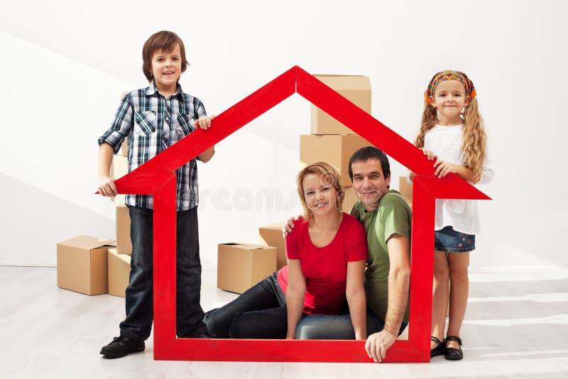 Glückliche Familie mit den Kindern, die in ihr neues Haus sich bewegen lizenzfreies stockfoto