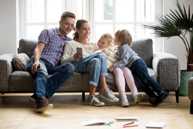 Glückliche Familie mit den Kindern, die mit on-line-Mobile-APP-toget kaufen lizenzfreies stockfoto