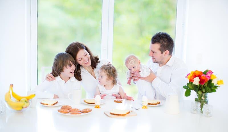 Glückliche Familie mit drei Kindern, die Frühstück genießen stockbild