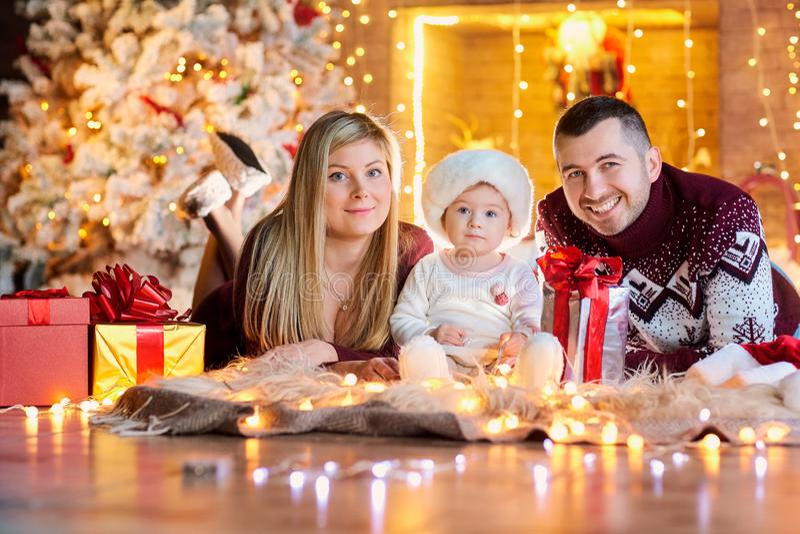 Glückliche Familie mit einem Baby in einem Weihnachtsraum stockbild