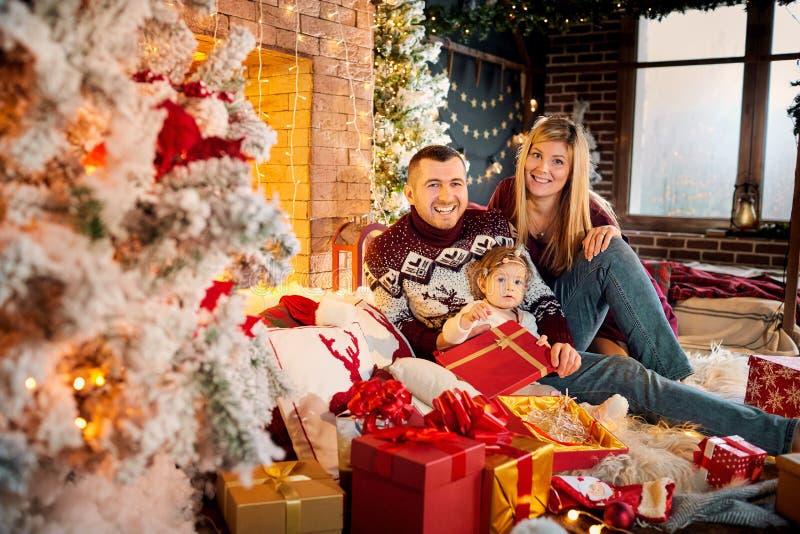Glückliche Familie mit einem Baby in einem Weihnachtsraum stockfotos