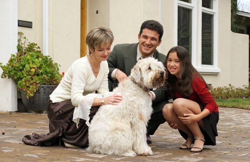 Glückliche Familie mit einem Hund stockfotografie