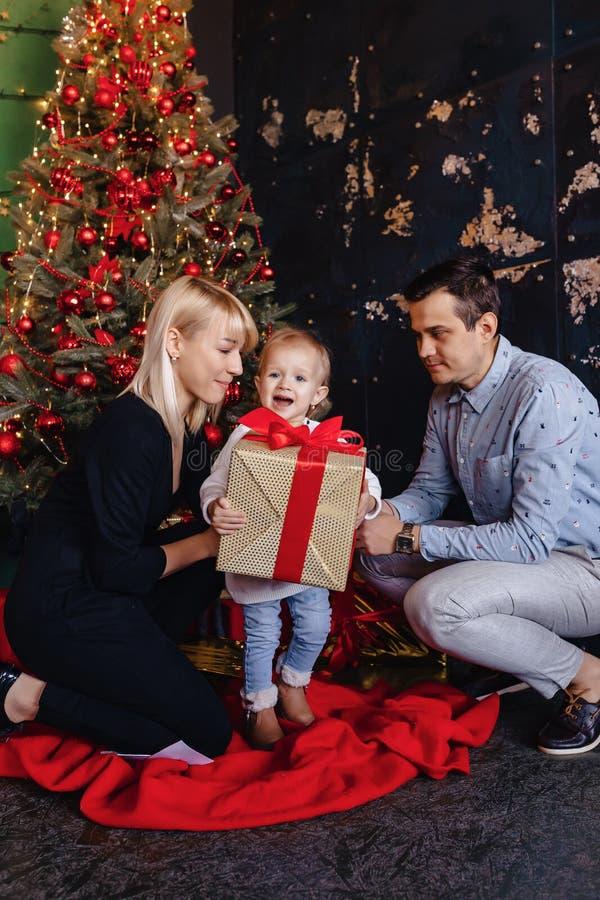 Glückliche Familie mit einem Kind feiern das neue Jahr nahe dem Weihnachtsbaum stockfotos