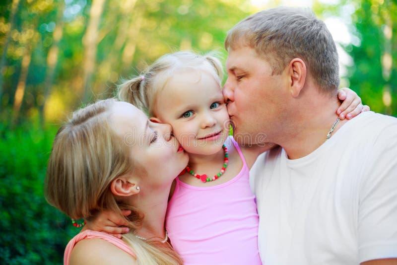 Glückliche Familie mit einem Kind im Freien stockfotografie
