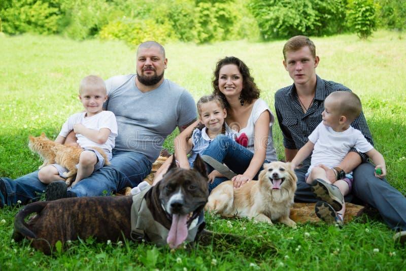 Glückliche Familie mit Hunden und Katze stockbild