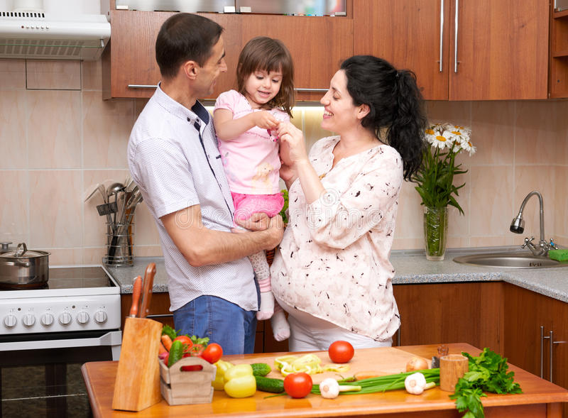 Glückliche Familie mit Kind im Hauptkücheninnenraum mit frischen Obst und Gemüse, schwangere Frau, gesundes Lebensmittelkonzept stockfotografie