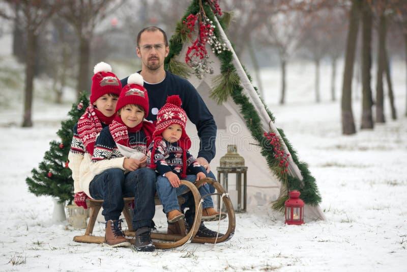 Glückliche Familie mit Kindern, den Spaß im Freien im Schnee auf Christus habend stockbilder