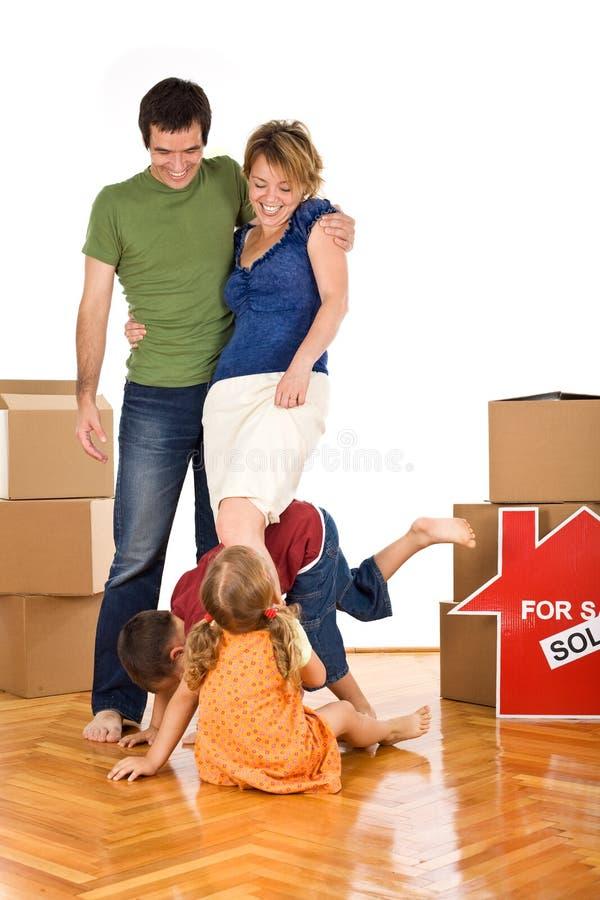 Glückliche Familie mit Kindern in ihrem neuen Haus lizenzfreie stockfotografie