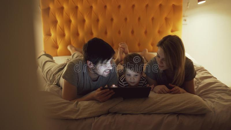 Glückliche Familie mit kleinem Sohn im Bett zu Hause liegen und Anwendung des Tablet-Computers für aufpassenden Karikaturfilm bev lizenzfreie stockfotografie