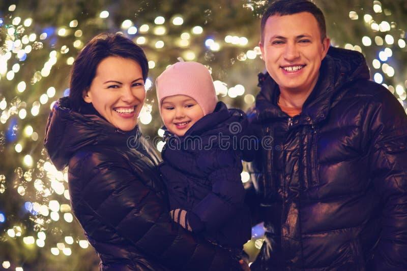 Glückliche Familie mit kleiner Tochter über Weihnachtshintergrund stockfoto