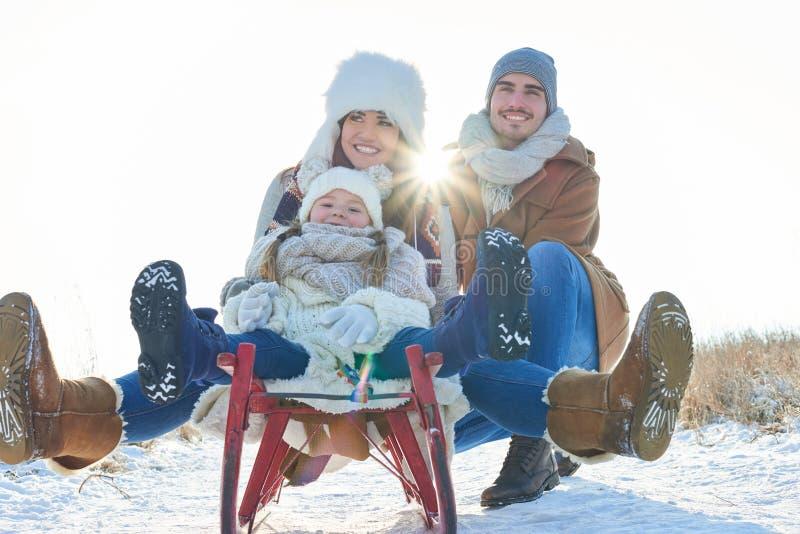 Glückliche Familie mit Schlitten im Winter lizenzfreie stockfotografie