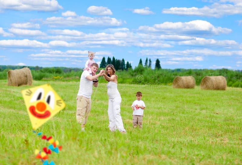 Glückliche Familie mit schwangerem Fraufliegendrachen stockfotos