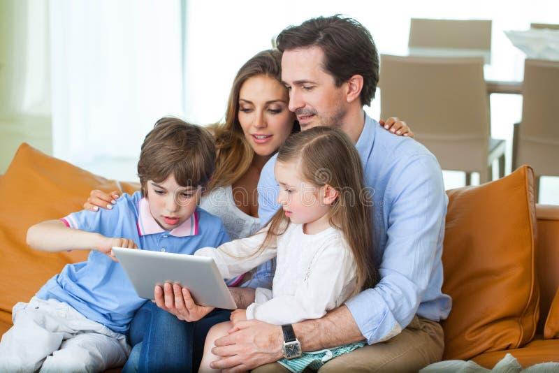 Glückliche Familie mit Tabletten-PC lizenzfreie stockbilder