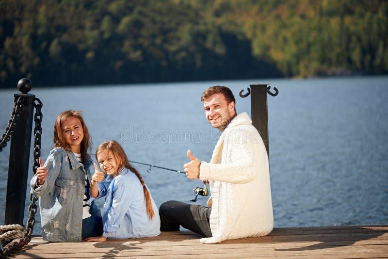 Glückliche Familie mit Tochterfischen im Teich im Fall lizenzfreies stockfoto