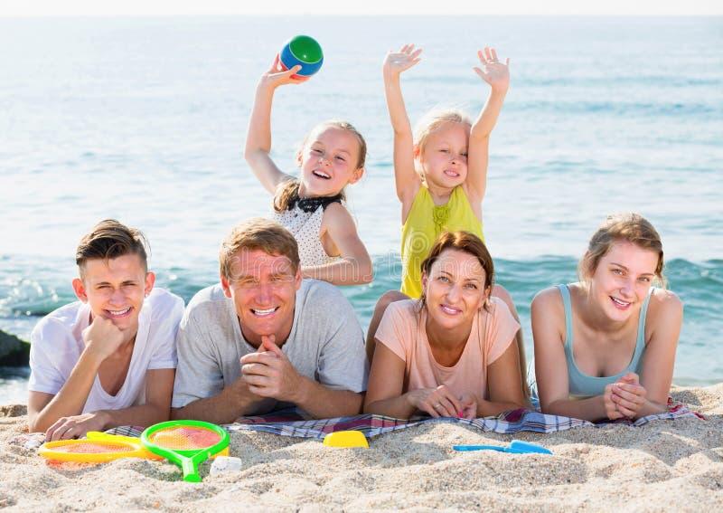 gl ckliche familie mit vier kindern die auf strand liegen. Black Bedroom Furniture Sets. Home Design Ideas