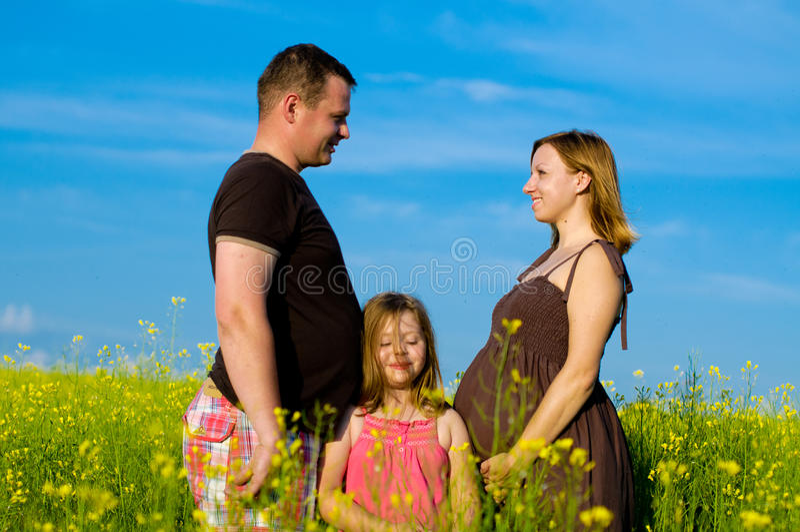 Glückliche Familie mit Wolken und Gras stockfoto