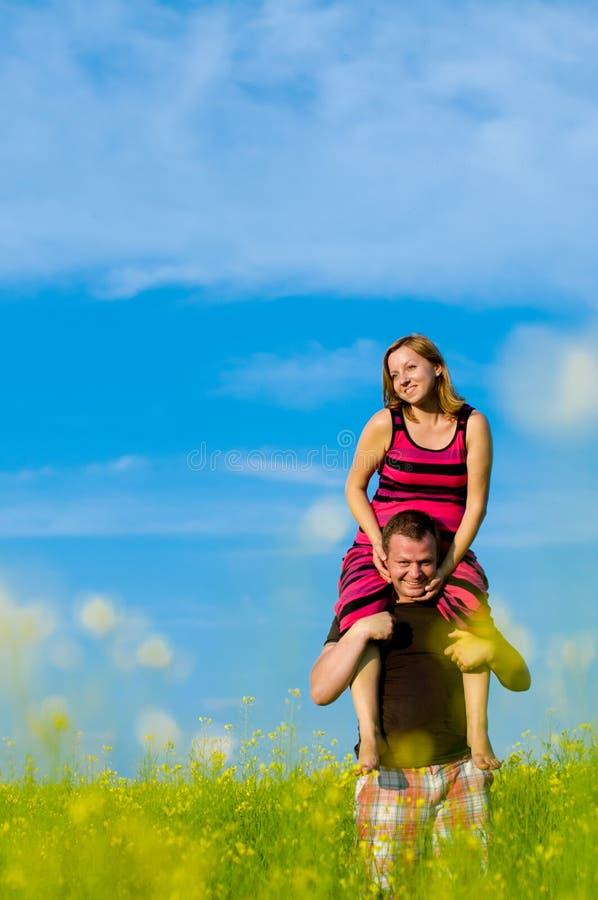 Glückliche Familie mit Wolken und Gras stockfotografie