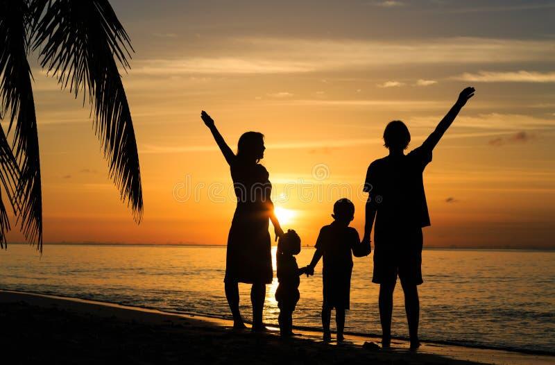 Glückliche Familie mit zwei Kindern auf dem Sonnenuntergang tropisch stockfotografie