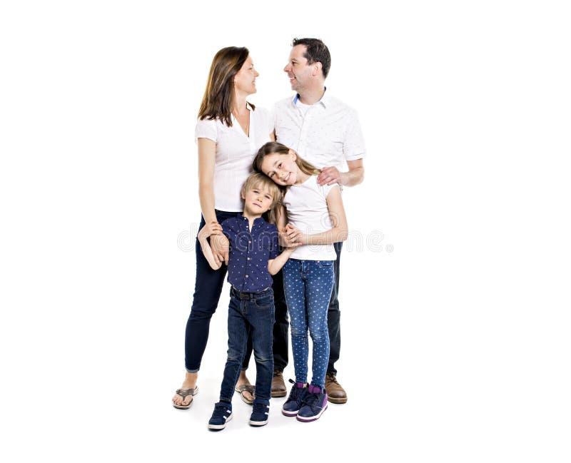 Glückliche Familie mit zwei Kindern auf Studioweißhintergrund stockfotos