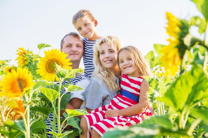 gl ckliche familie mit zwei kindern in den sonnenblumen. Black Bedroom Furniture Sets. Home Design Ideas