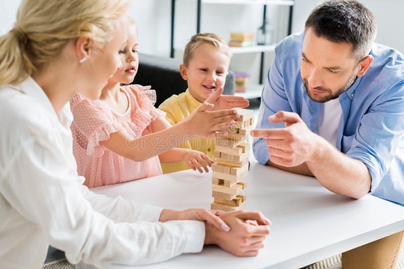 glückliche Familie mit zwei Kindern, die zu Hause mit Holzklötzen spielen lizenzfreie stockfotografie