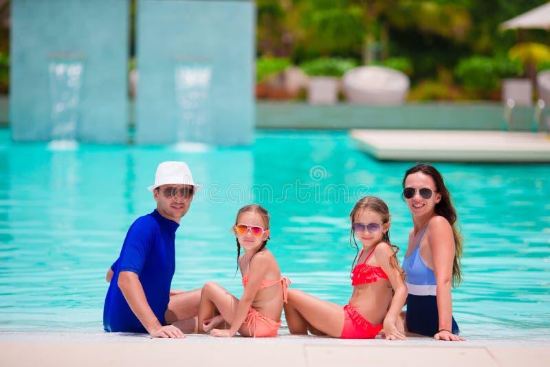 Glückliche Familie mit zwei Kindern im Swimmingpool Lächelnde Eltern und Kinder auf Sommerferienschwimmen und -c$haben des Spaßes lizenzfreie stockfotos