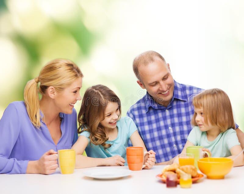 Glückliche Familie mit zwei Kindern mit Frühstücken stockbild