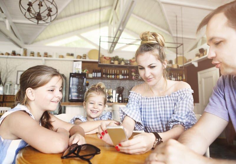 Glückliche Familie mit zwei Töchtern, die zu Abend essen und smartph verwenden lizenzfreies stockbild