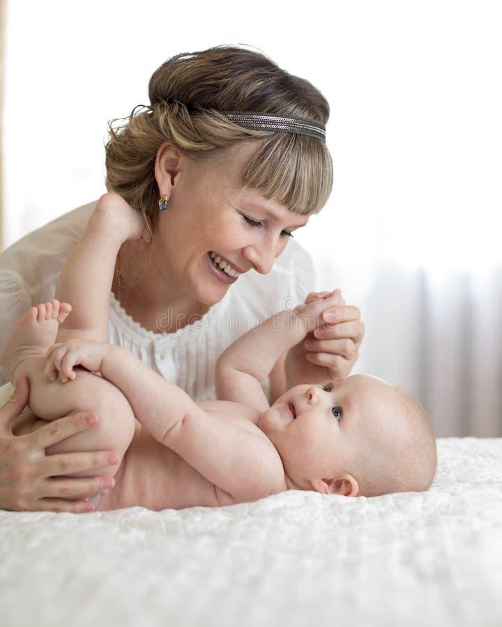 Mutter, Die Ihr Kleines Baby Massiert Stockfoto - Bild von