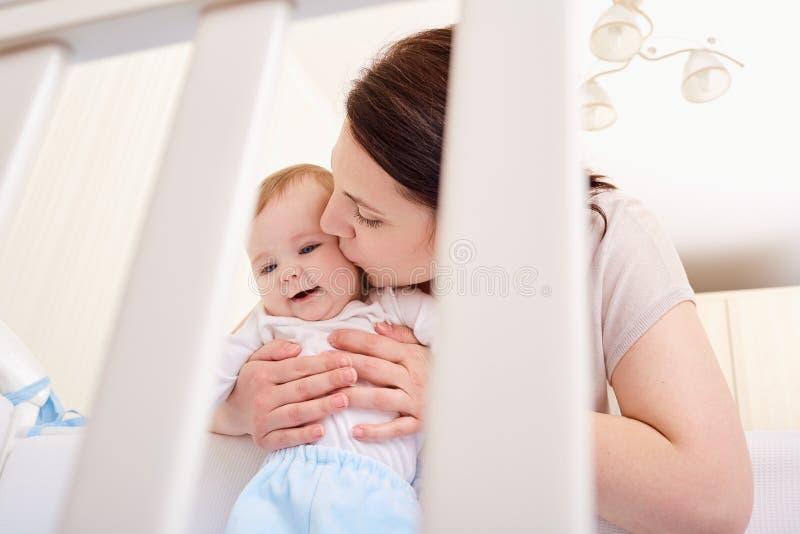 Glückliche Familie Mutter küsst Baby in einer Krippe lizenzfreies stockbild
